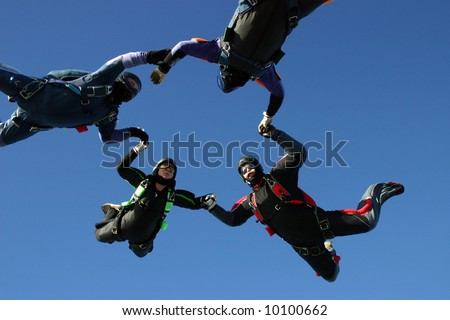 Four skydivers form a circle - stock photo