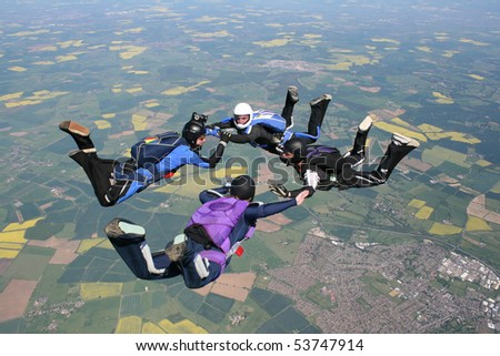 Four skydivers in freefall - stock photo