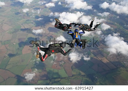 Four skydivers in freefall on a sunny day - stock photo