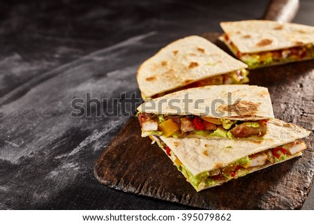 Four sliced wedges of meat and veggie filled quesadillas on worn out black cutting board over dark background with copy space - stock photo