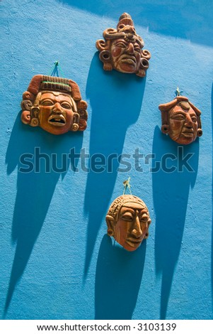 Four small ceramic masks hanging on a bright blue wall with long shadows from the equatorial sun. - stock photo