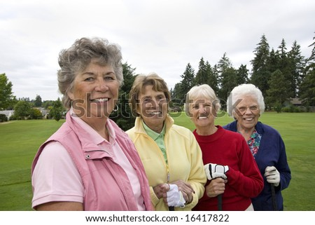 Four smiling, elderly women carrying golf clubs. Horizontally framed photo.