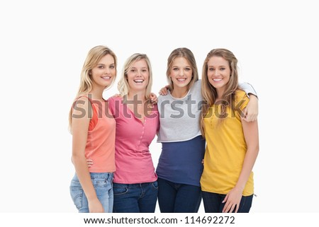 Four smiling friends as they stand beside one another - stock photo