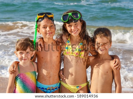 Four smiling kids enjoying on the beach