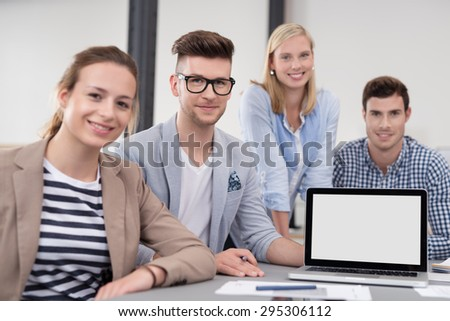 Four Smiling Office Workers Sitting at the Table with Laptop Computer, Emphasizing Copy Space on the Screen. - stock photo