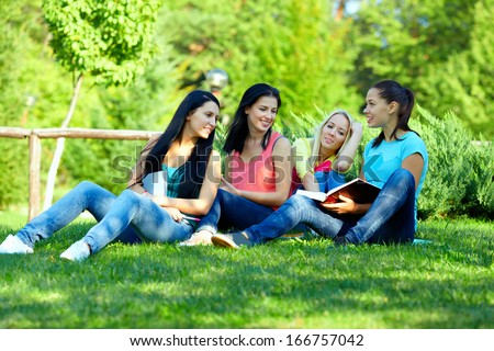 four smiling student girls studying in green park