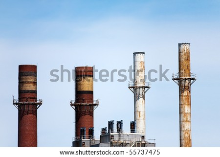 Four smoke stacks atop factories or industrial buildings in the skyline. - stock photo