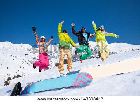 Four snowboarders friends in bright vivid clothes jumping in snow with mountains on background - stock photo