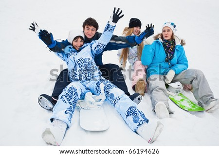 Four snowborders sit on snow and preparing to ride from the hill - stock photo