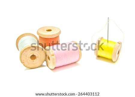four spools of thread with needle on white - stock photo