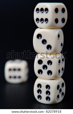 Four stacked dices and one single dice on black background - stock photo