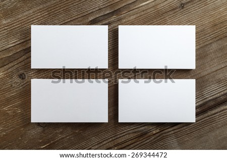 Four stacks of blank business cards on a dark wooden background. Mockup for branding identity. Clipping path. Top view. - stock photo