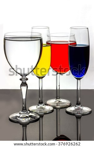 Four stemmed glasses containing bright color drinks