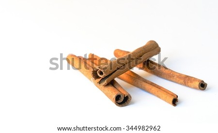 four sticks of cinnamon on white background