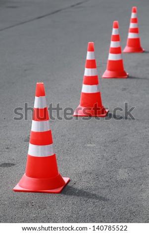 Four striped orange cones stand on gray asphalt road - stock photo