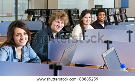 Four students studying in cubicles in a public library, with focus on the second young adult man - stock photo