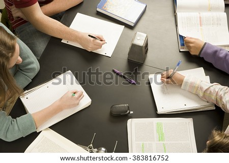 Four students working in a classroom - stock photo