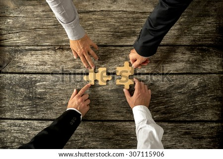 Four successful business men joining two puzzle pieces each being held by two partners, rustic wooden background. Conceptual of merger or creative cooperation of two business companies. - stock photo