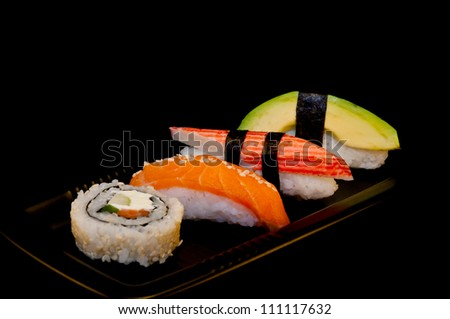 Four sushi on a black plate