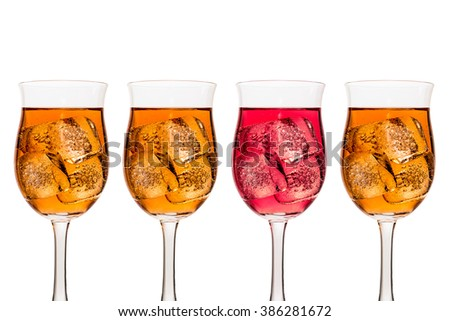 Four tall wine glasses containing amber and red coloured liquid wine and ice cubes shown in a single row with three amber and one red showing odd one out red for danger. - stock photo