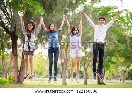 Four teenage friends jumping outdoors - stock photo