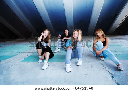 Four teenage friends sitting on concrete slabs - stock photo