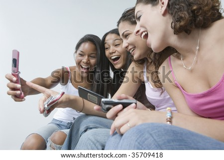 Four teenage girls looking at pictures on a mobile phone and smiling - stock photo