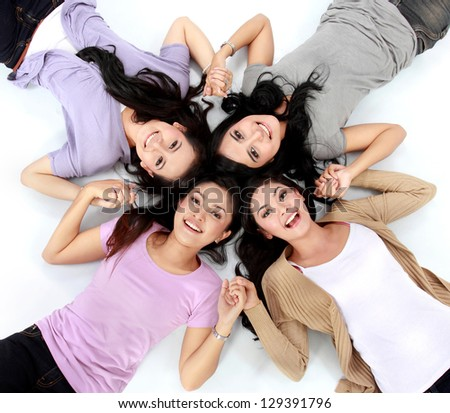 four teenage girls lying on the floor smiling - stock photo
