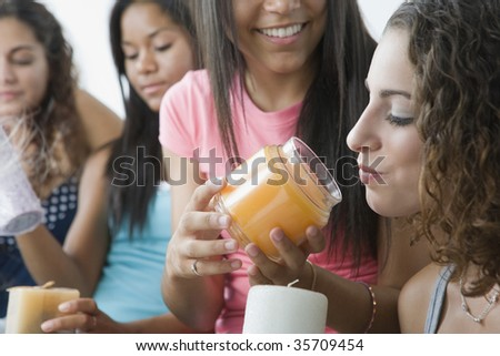 Four teenage girls playing with scented candles - stock photo