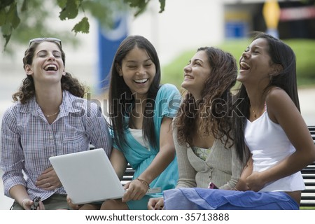Four teenage girls sitting on a bench and smiling in the school campus - stock photo