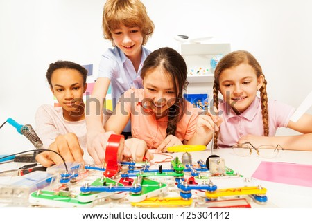 Four teenage students making a physical test - stock photo