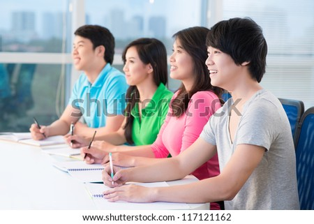 Four teenagers sitting at seminar and listening to teacher - stock photo