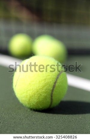 Four tennis balls on green tennis court