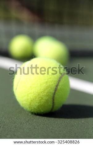 Four tennis balls on green tennis court - stock photo