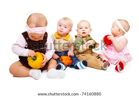 Four toddlers holding colorful peppers in hands - stock photo