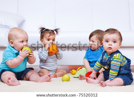 Four toddlers sitting in a lounge - stock photo