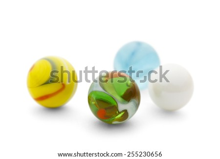 Four Toy Glass Marbles Isolated on a White Background. - stock photo