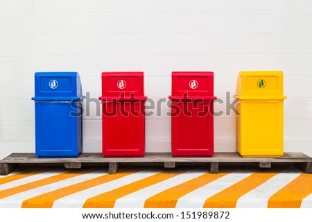 Four trash cans for collecting different type of waste installing beside the wall - stock photo