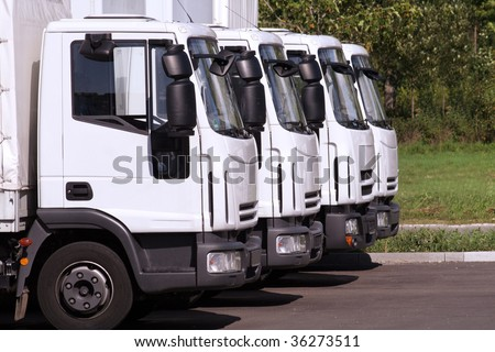four trucks of a transporting company in a row - stock photo