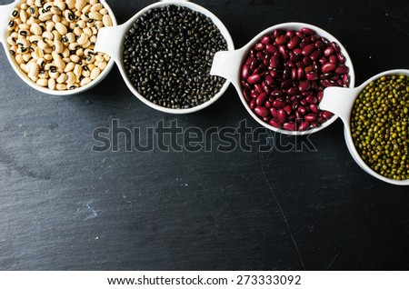 Four types of dry beans  on the black stone backgroud - stock photo