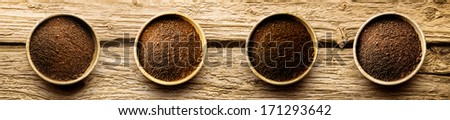Four varieties of freshly ground coffee powder in individual dishes showing medium and full roast on a cracked weathered driftwood background, overhead view in banner format - stock photo