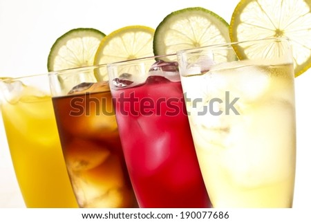 Four various colored beverages with ice cubes and lemon and lime slices. - stock photo