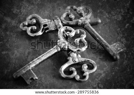 Four vintage keys. Retro aged toned photo with scratches. Black and white. - stock photo
