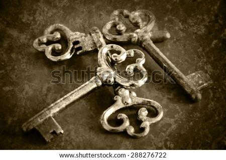 Four vintage keys. Retro aged toned photo with scratches. Sepia. - stock photo