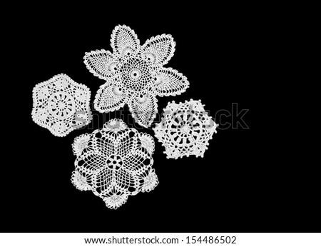 Four vintage white crocheted mats on black background - stock photo