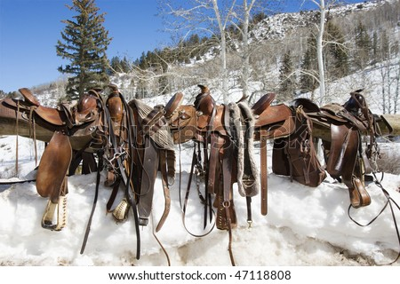 Four Western saddles sitting on a rail with a snowy landscape in the background. Horizontal shot. - stock photo