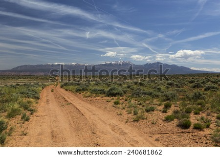 Four wheel drive trail across the desert to Moab Utah with the La Sal Mountains in the distance. - stock photo