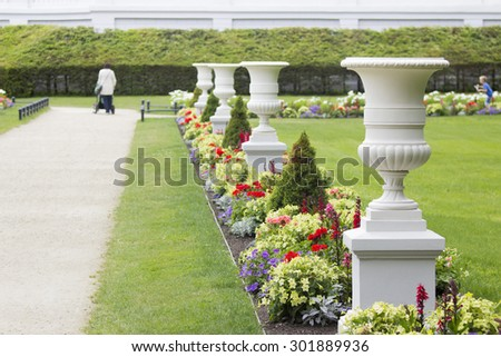 Four white antique vases in a resort park in summer