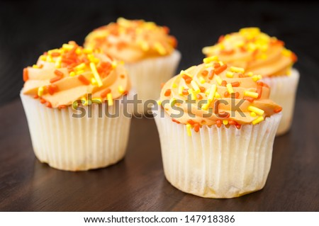 Four white cupcakes with orange icing and yellow and orange sprinkles - stock photo