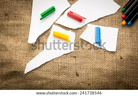 Four white paper pieces decorated with four different colours